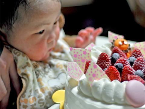 デコレーションケーキに手を伸ばす息子