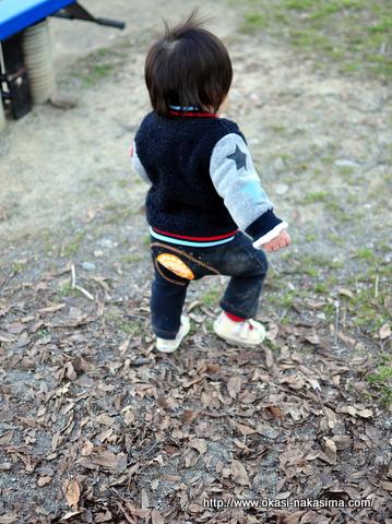 枯葉の上を歩く息子