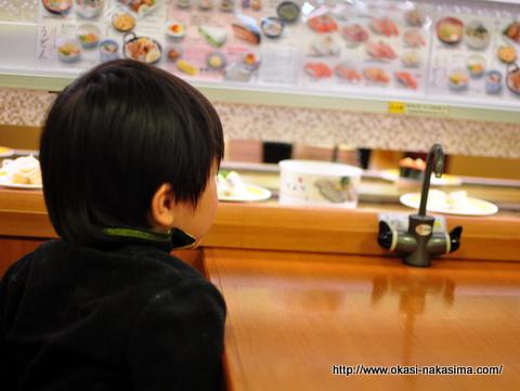 お寿司のレーンを見つめる息子